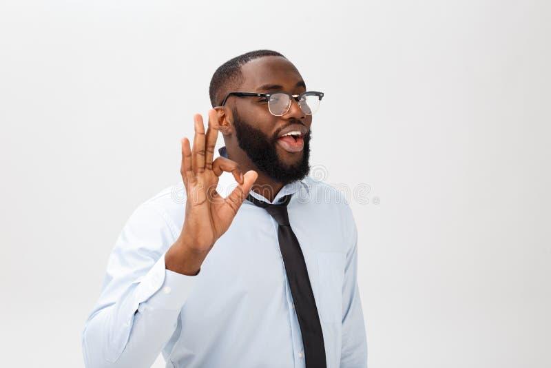 Junger schwarzer Geschäftsmann, der glücklichen Blick, lächelnd, Gestikulieren hat und zeigen OKAYzeichen Afrikanische männliche  lizenzfreie stockfotografie