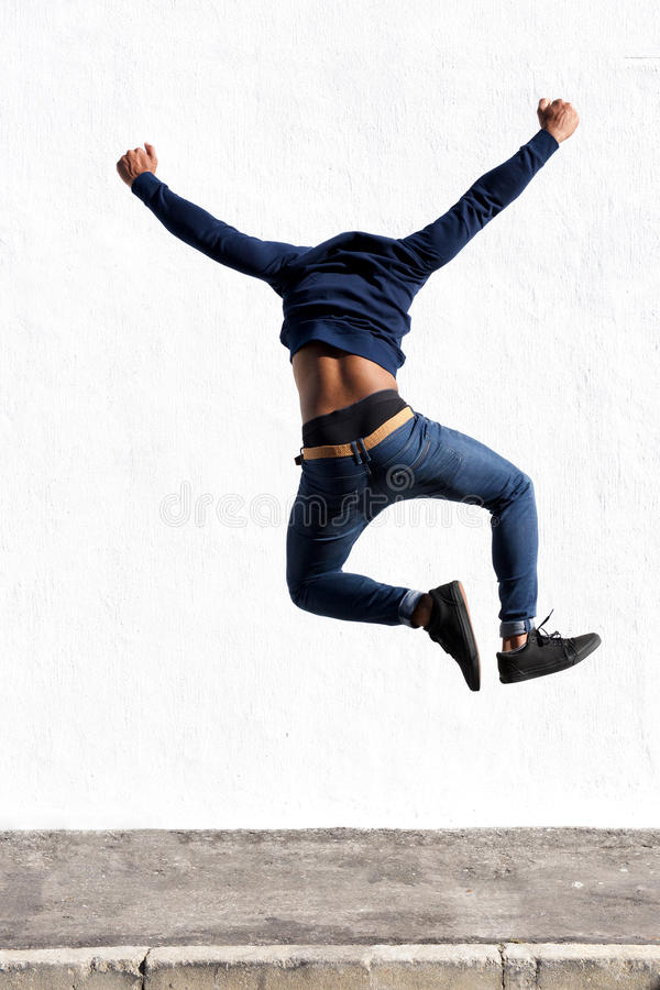 Junger schwarzer Mann, der draußen in einer Luft auf Bürgersteig springt stockfotografie