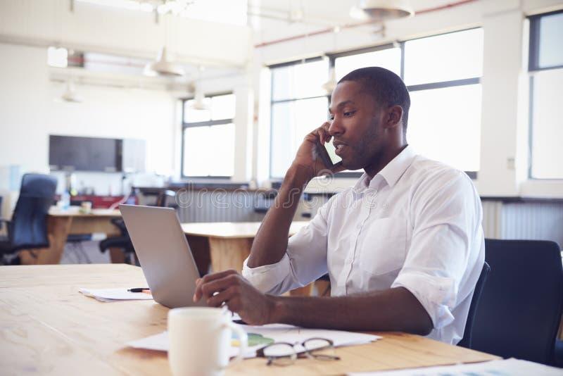 Junger schwarzer Mann, der im Büro mit Laptop unter Verwendung des Telefons arbeitet lizenzfreie stockfotografie