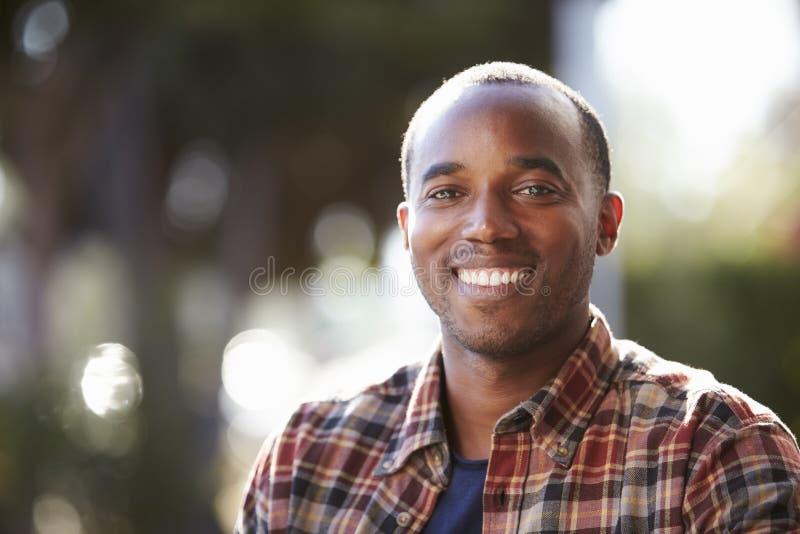 Junger schwarzer Mann draußen, Haupt- und Schulter, derporträt sitzt lizenzfreie stockbilder