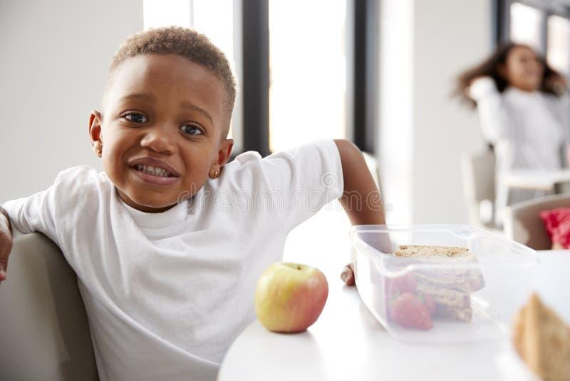 Junger schwarzer Schüler, der an einem Tisch oben lächelt in einem Kindergartenklassenzimmer während seiner Mittagspause, Abschlu stockbilder