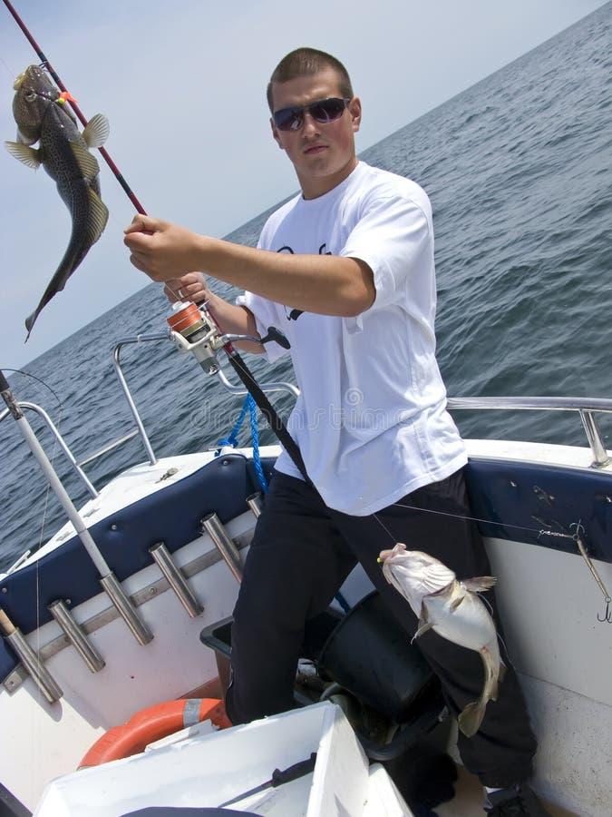 Junger Seefischer mit Kabeljaus stockbild