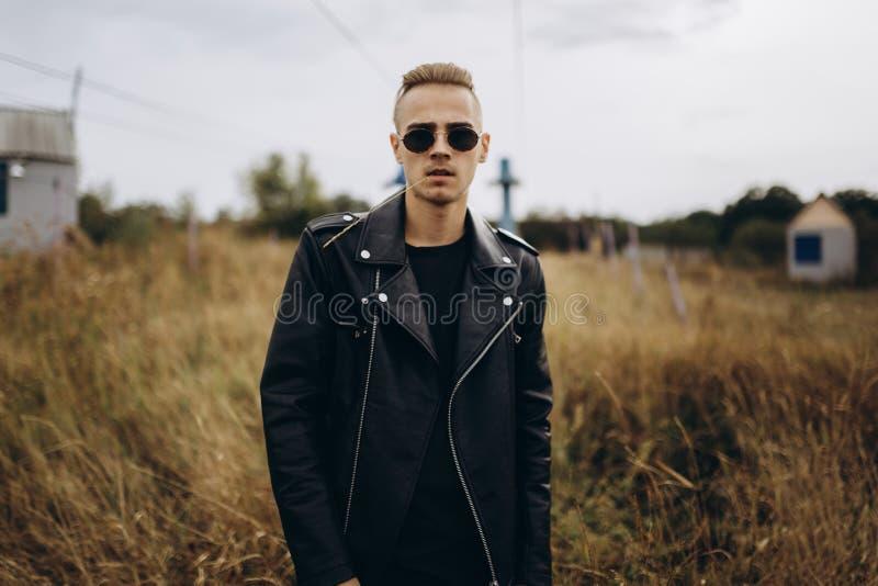 Junger sexy Mann in der Lederjacke und in Sonnenbrille, die im Freien steht stockfotografie