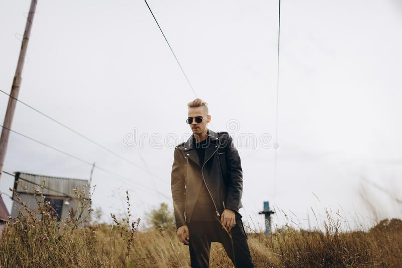 Junger sexy Mann in der Lederjacke und in Sonnenbrille, die im Freien steht lizenzfreie stockbilder