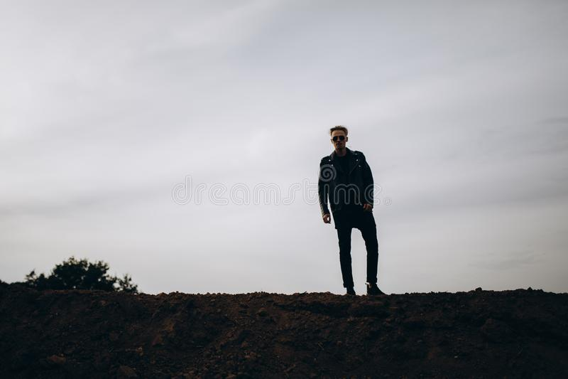 Junger sexy Mann in der Lederjacke und in Sonnenbrille, die im Freien steht Dunkles Schattenbild gegen grauen Himmel lizenzfreies stockfoto