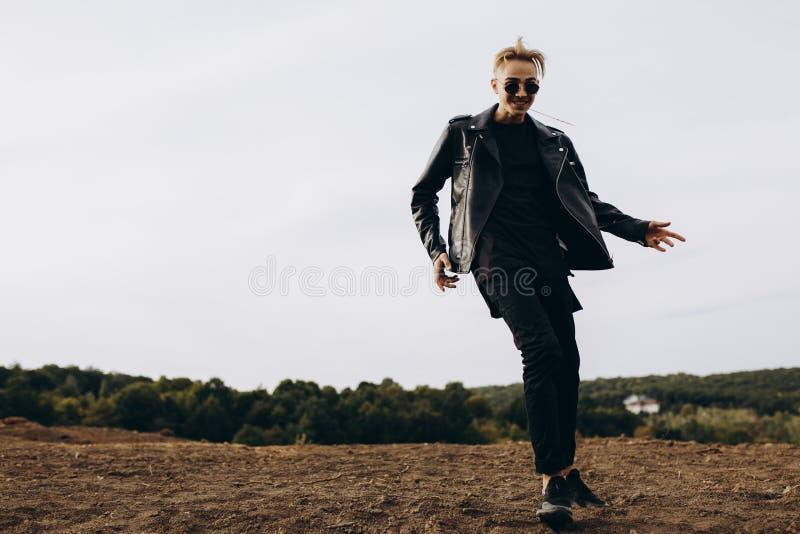 Junger sexy Mann in der Lederjacke und in Sonnenbrilletanzen im Freien Schattenbild gegen grauen Himmel stockfotografie