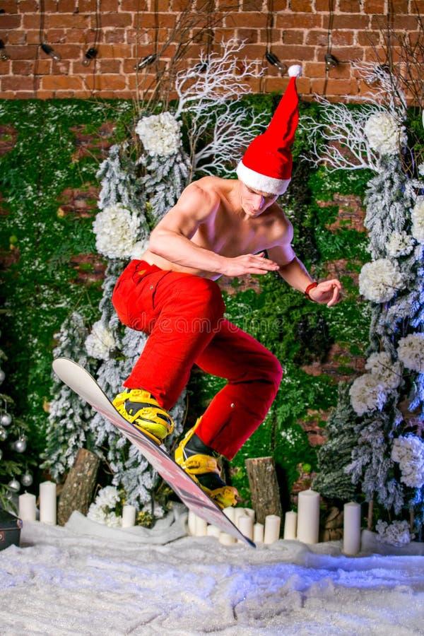 Junger sexy sportlicher junger Mann in den roten Hosen und in Sankt-Hut, die mit einem Snowboard springt lizenzfreie stockfotos