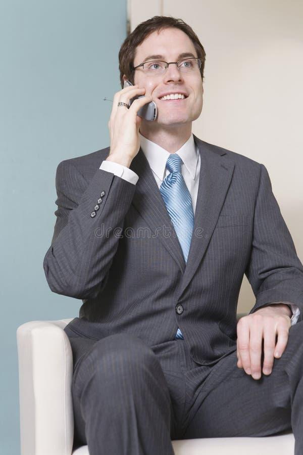 Junger Sitzgeschäftsmann in einer grauen Klage. lizenzfreies stockbild
