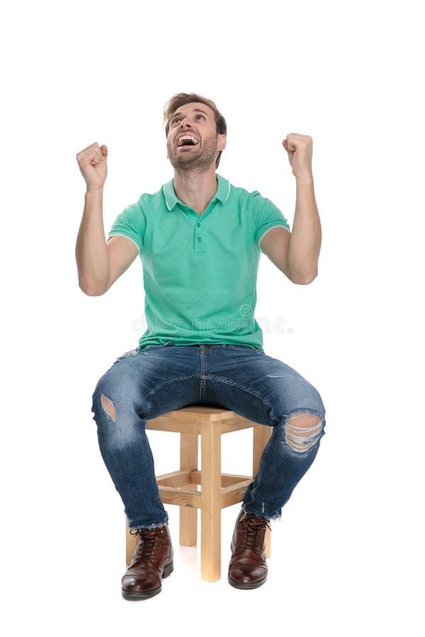 Junger Sitzmann, der mit den Händen in der Luft schreit stockfotos