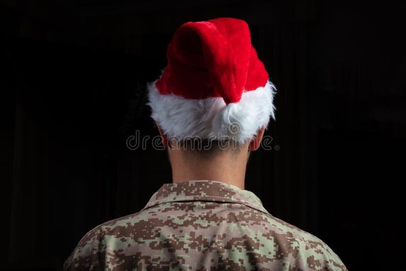 Junger Soldat, der Sankt-Hutstellung auf schwarzem Hintergrund trägt stockfotos