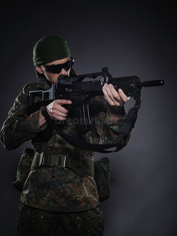 Junger Soldat in der Tarnung mit einer Gewehr. lizenzfreies stockbild