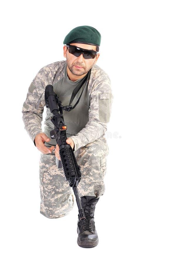 Junger Soldat mit dem Barett und Gläsern, die ein Maschinengewehr halten stockfotos