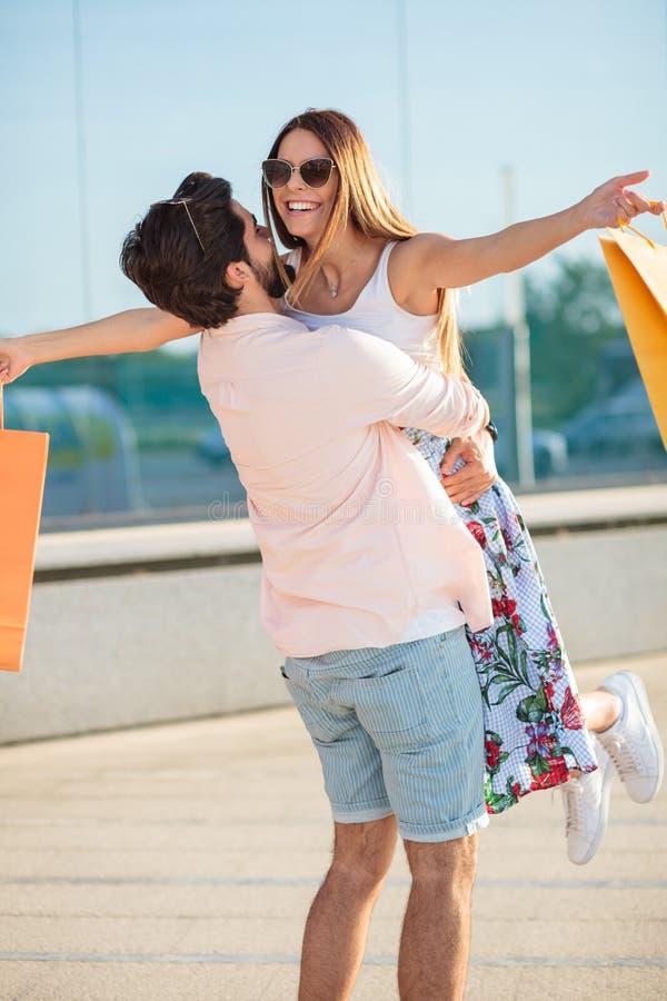 Junger spielerischer Mann, der seine Freundin in der Luft spinnt stockbild