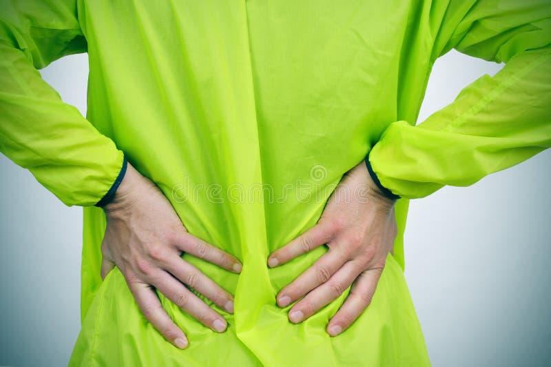 Junger Sportler mit Rückenschmerzen stockbild