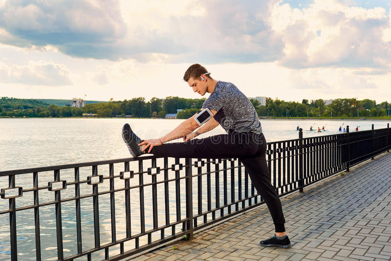Junger Sportlerläufer, der Beine vor Lauf ausdehnt lizenzfreie stockfotografie