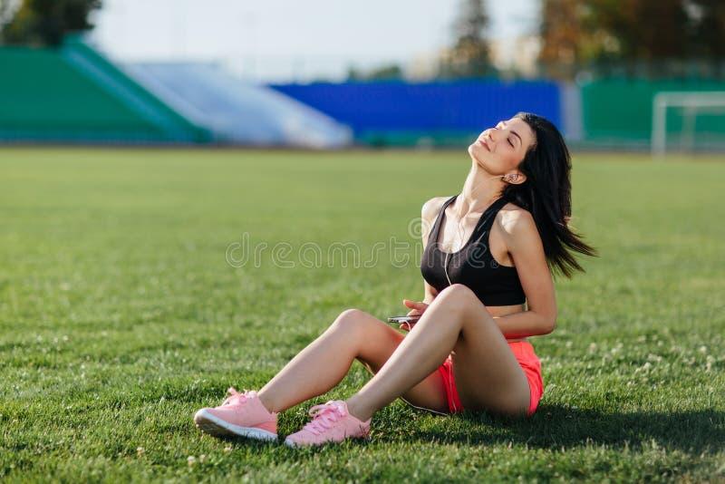 Junger sportlicher Frau Brunette im Sportkleid, das auf dem Grasfußballplatzstadion sitzt und hört Musik in den Kopfhörern, ihren stockbild