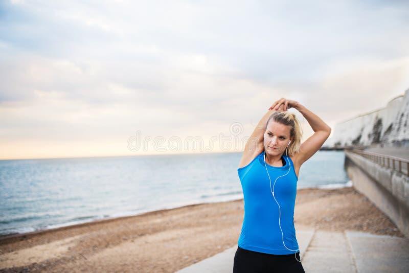 Junger sportlicher Frauenläufer mit den Kopfhörern, die draußen auf dem Strand, dehnend stehen aus lizenzfreies stockfoto