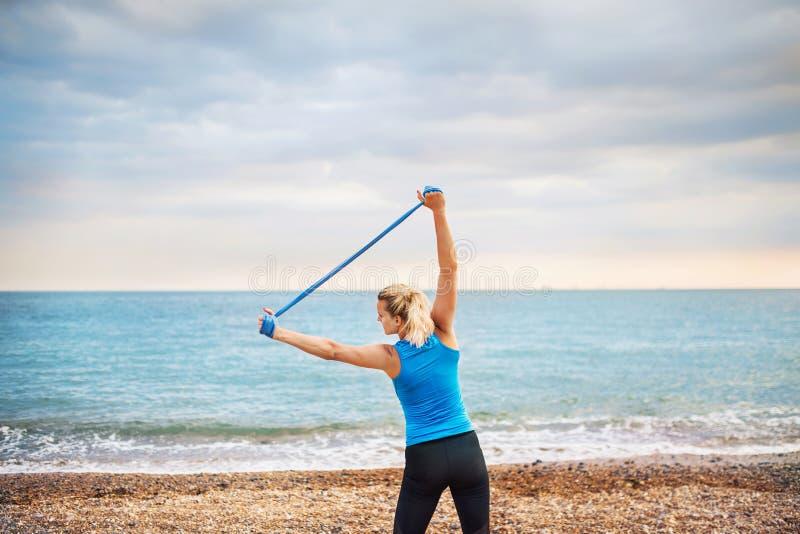 Junger sportlicher Frauenläufer mit Gummibändern draußen auf einem Strand, trainierend lizenzfreies stockbild