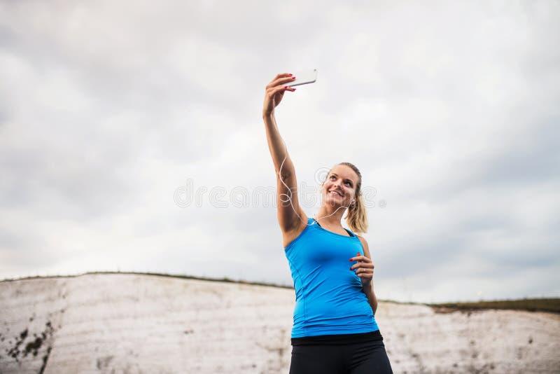 Junger sportlicher Frauenläufer mit Kopfhörern und Smartphone auf dem Strand, selfie nehmend lizenzfreies stockfoto