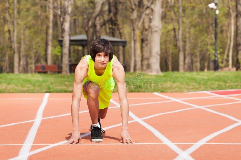 Junger sportlicher Junge in Anfangsposition an der Rennbahn stockfoto