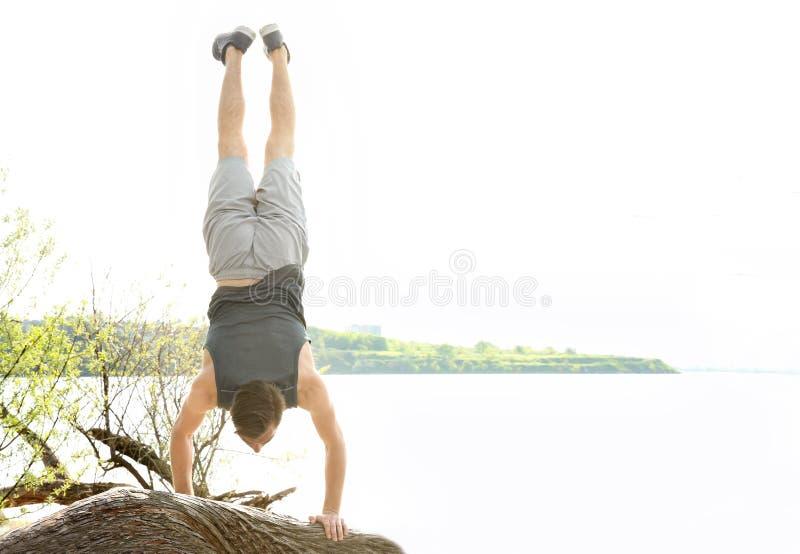 Junger sportlicher Mann, der akrobatische Übungen tut lizenzfreies stockbild