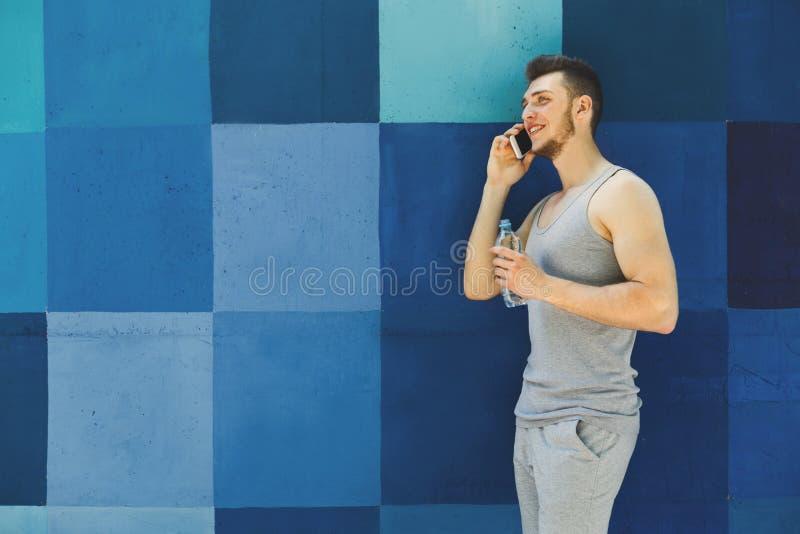 Junger sportlicher Mann, der am Telefon spricht stockfotos