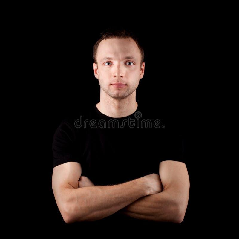 Junger sportlicher Mann im schwarzen T-Shirt auf Schwarzem lizenzfreies stockbild