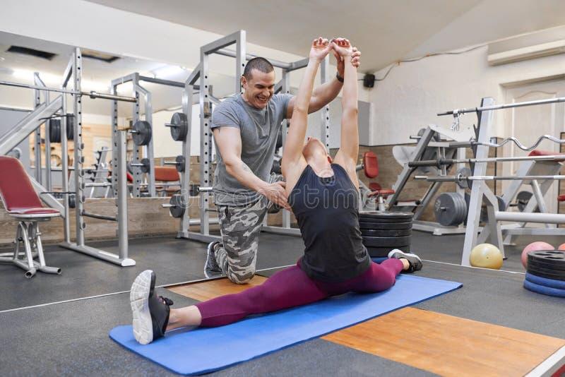 Junger starker muskulöser Mann, welche der jungen athletischen Frau ausdehnt auf Yogamatte in der Turnhalle hilft lizenzfreies stockbild