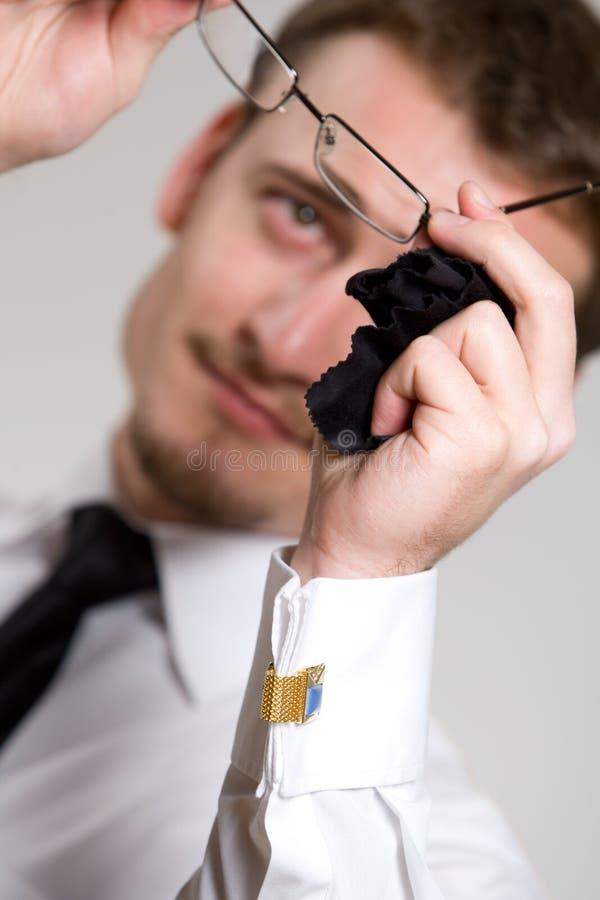 Junger stattlicher Geschäftsmann, der Brillen abwischt lizenzfreies stockbild