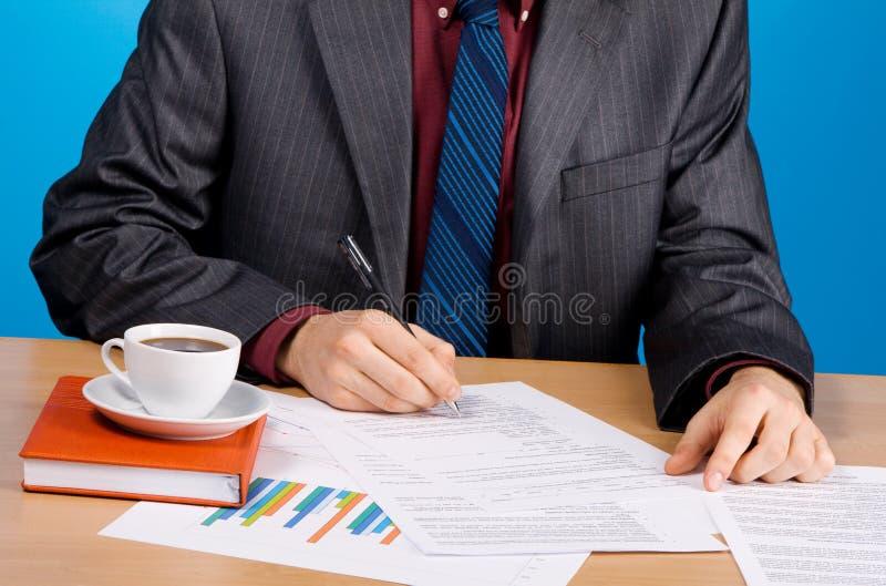 Junger stattlicher Geschäftsmann, der mit Dokumenten arbeitet stockfotos