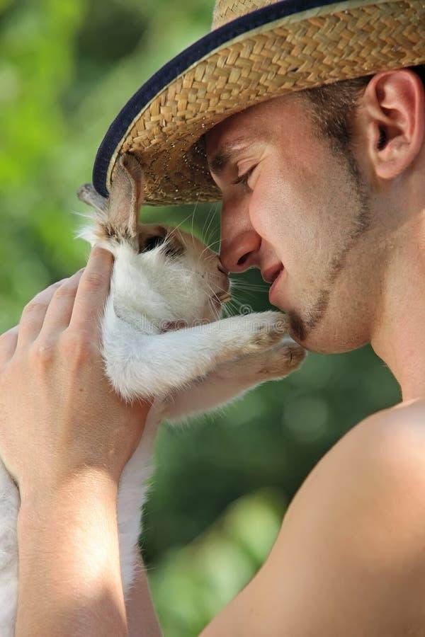 Junger stattlicher Mann, der sein Haustierkaninchen anhält lizenzfreie stockbilder