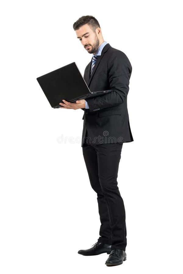 Junger stehender Geschäftsmann, der an einem Laptop arbeitet lizenzfreie stockfotografie