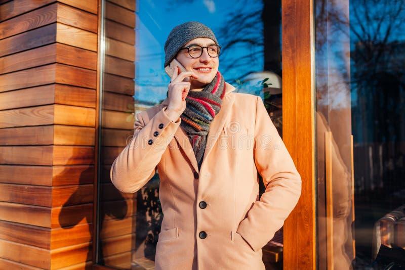 Junger stilvoller Geschäftsmann, der Smartphone verwendet und durch Café nennt H?bscher Kerl, der klassische Kleidung und Zus?tze lizenzfreie stockfotografie