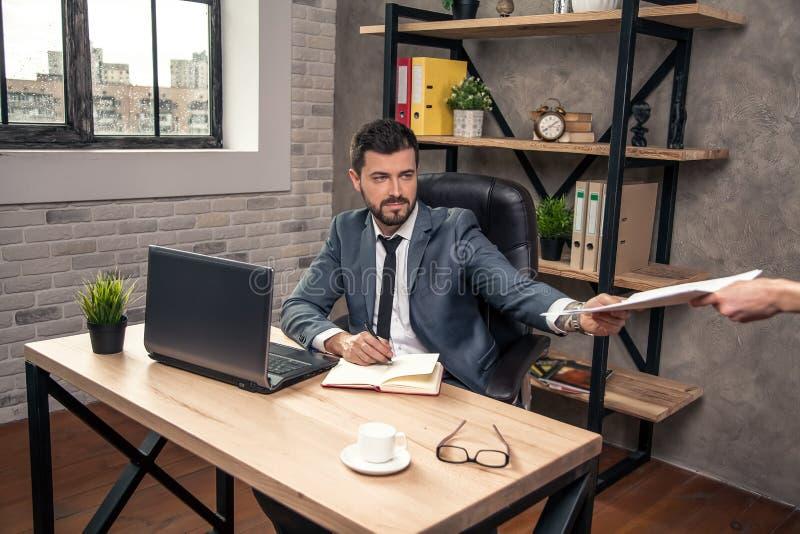 Junger stilvoller hübscher Geschäftsmann an seinem Schreibtisch im Büro erhält einige Dokumente von seinem Sekretär stockbild