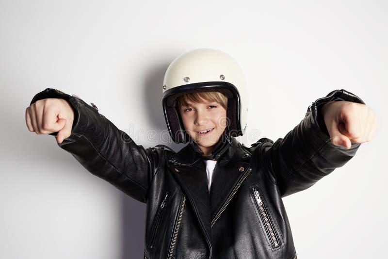 Junger stilvoller Kinderjunge in der schwarzen Lederjacke und in weißem moto Sturzhelm vortäuschend, ein Motorrad auf Weiß vorbei stockbild