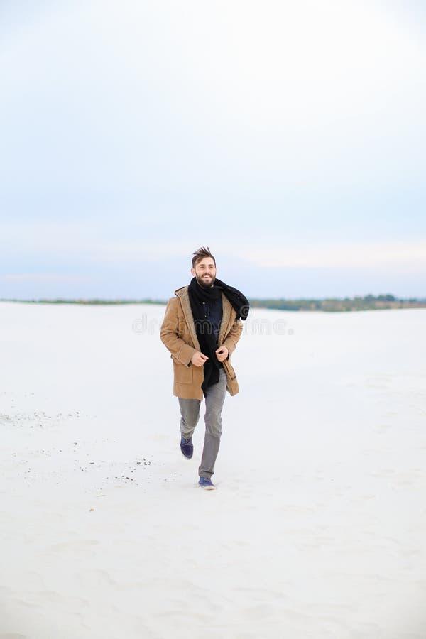 Junger stilvoller Mann, der braunen Mantel und den Schal läuft auf Schnee trägt stockfotografie