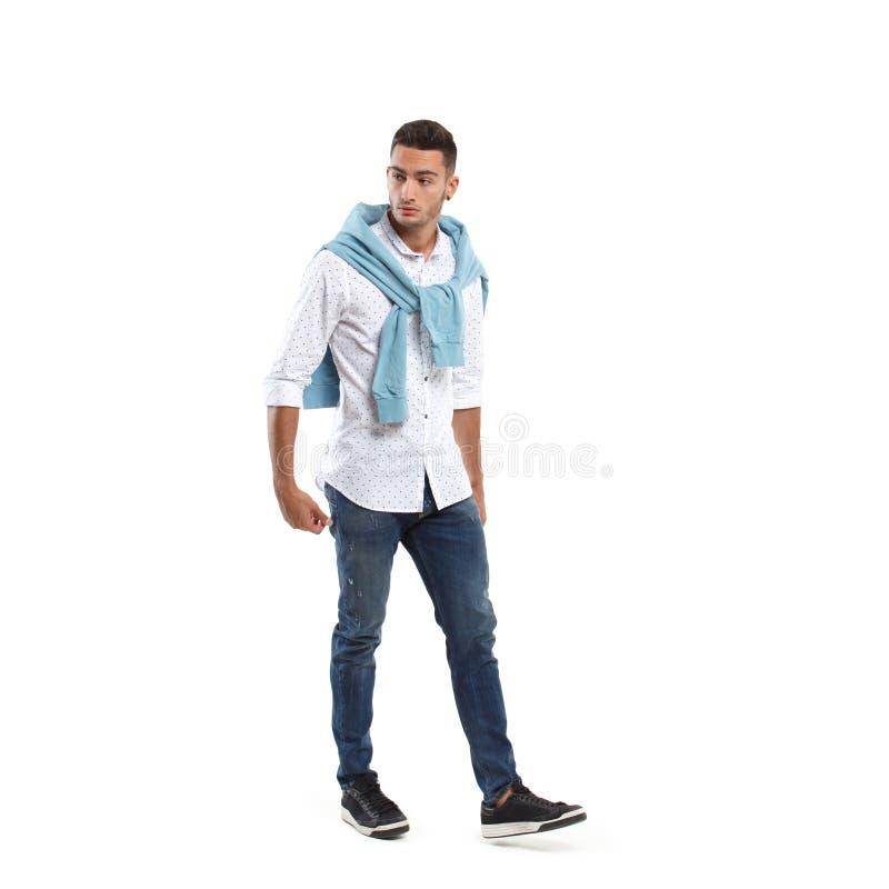 Junger stilvoller Mann gekleidet in einem weißen Hemd und in einer blauen Strickjacke drapiert über seinen Schultern und Jeanshal lizenzfreie stockfotos