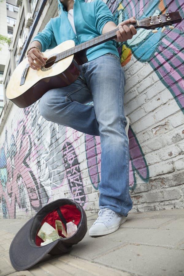 Junger Straßenmusiker, der Gitarre spielt und für Geld vor einer Wand mit Graffiti busking lizenzfreie stockbilder
