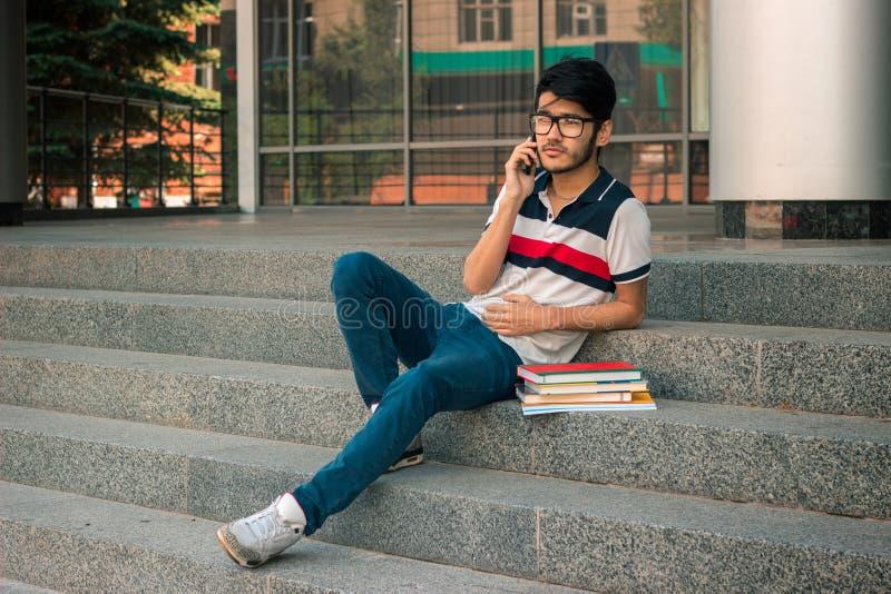 Junger Student, der auf der Treppe mit Büchern und den Gebührn für Telefon sitzt lizenzfreie stockfotos