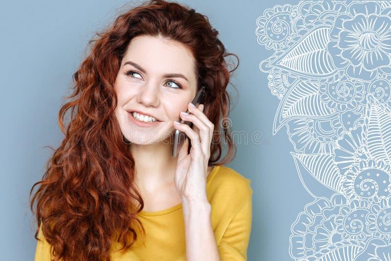 Junger Student, der beim Haben eines Telefongespräches froh schaut stockfoto
