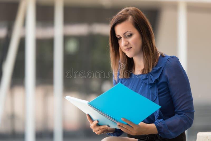 Junger Student, der ein blaues Buch liest stockfotos