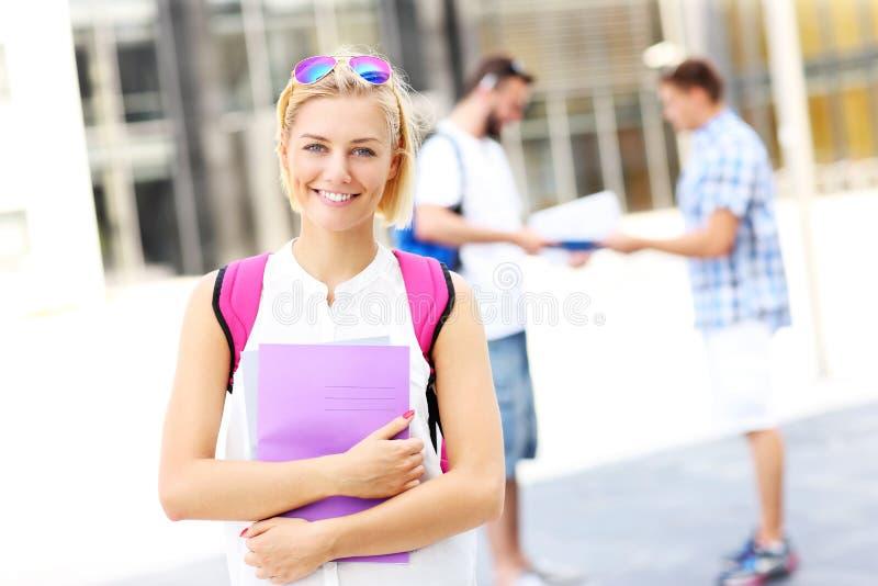 Junger Student, der im Campus steht und lächelt stockfoto