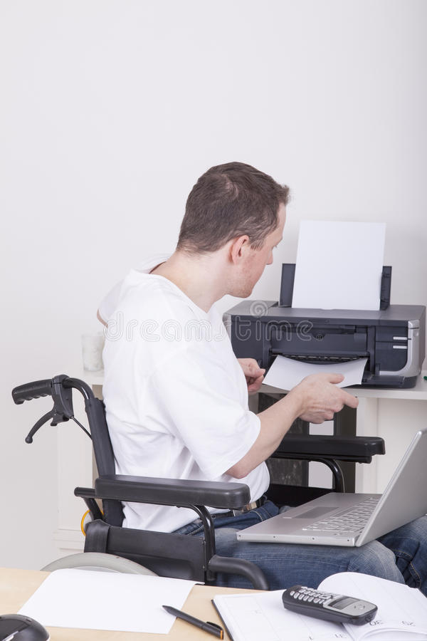 Junger Student im Büro des Rollstuhls zu Hause lizenzfreie stockbilder