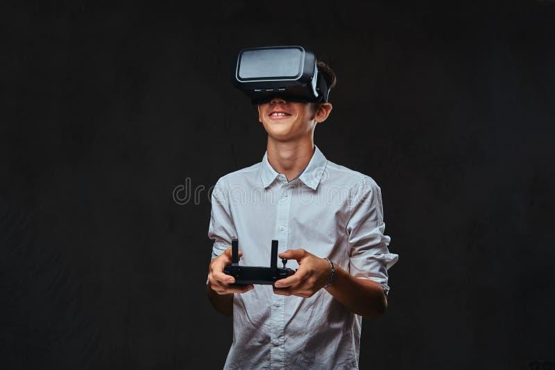 Junger Student kleidete in einem weißen Hemd unter Verwendung der Gläser der virtuellen Realität an und hält eine quadcopter Steu stockfotos