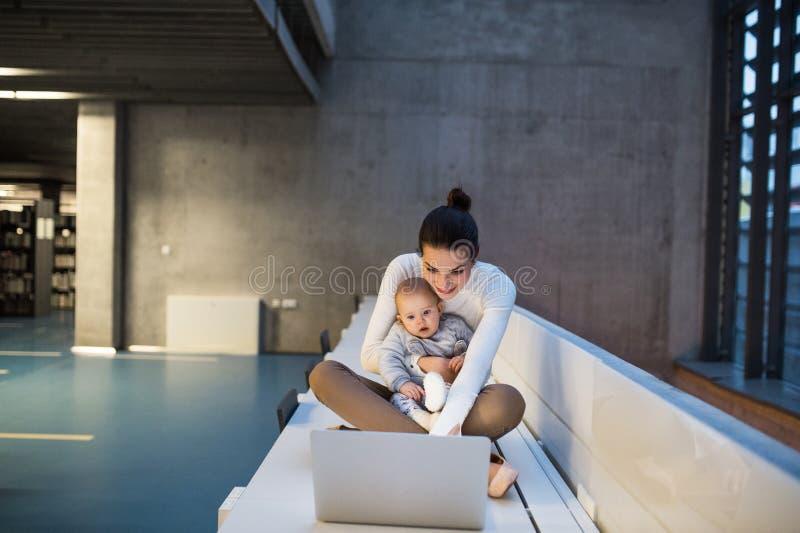 Junger Student mit einem Baby, das auf Schreibtisch im Raum in einer Bibliothek oder in einem Büro, unter Verwendung des Laptops  stockfoto