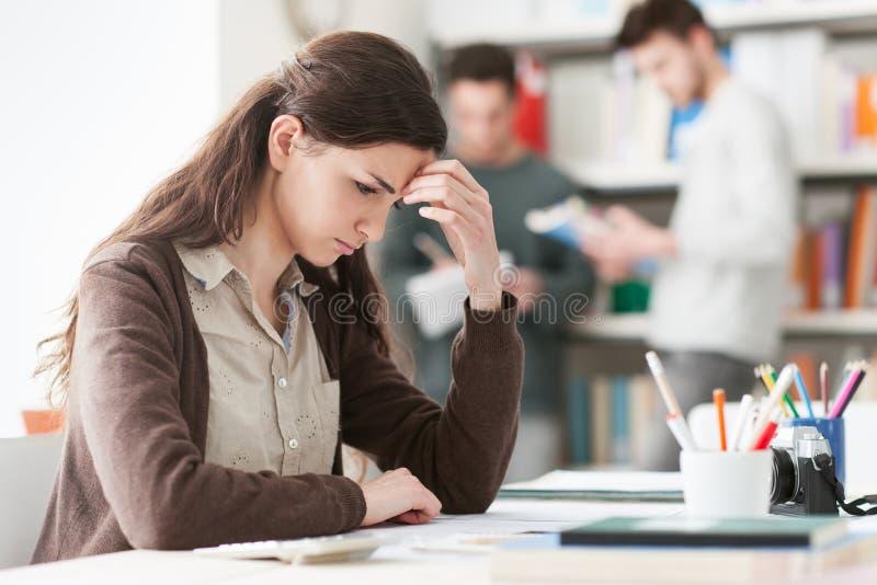 Junger Student mit Kopfschmerzen lizenzfreie stockbilder