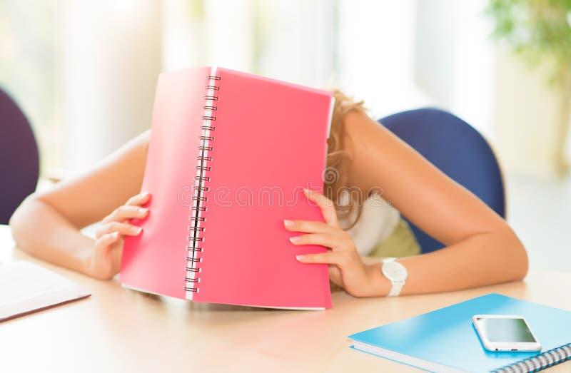 Junger Student schlafend auf dem Tisch mit einem Lehrbuch lizenzfreie stockfotografie