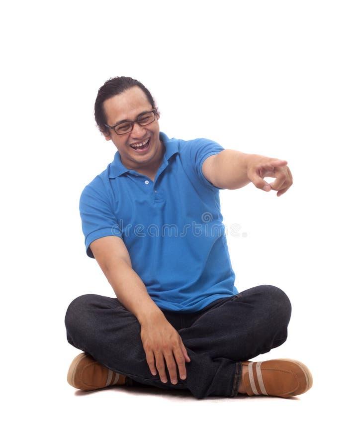 Junger Student Sit auf Boden und dem Lachen lizenzfreies stockbild