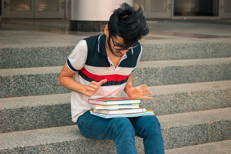 Junger Student sitzt auf den Schritten und betrachtet Bücher stockbild