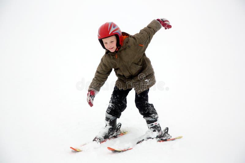 Junger Studentenjunge übt Skisportbewegungen Weißer Schneehintergrund stockbild
